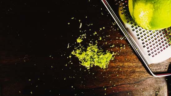 Die Limette gründlich waschen, abtrocknen und mit der Zestenreibe die Zesten von der Limette abreiben.