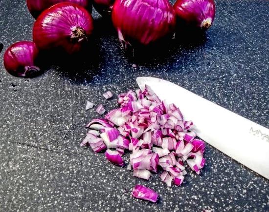 Nun die roten Zwiebeln schälen und in Würfel schneiden.