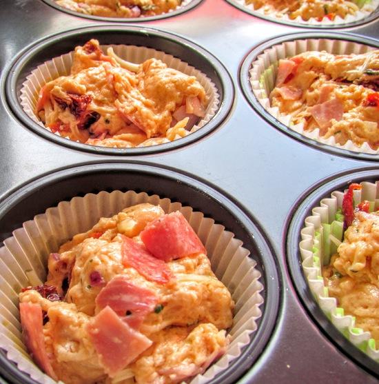 Anschließend die Tomatenölmischung mit den italienischen Kräutern sowie den geriebenen Käse hinzufügen und unter den Teig heben.