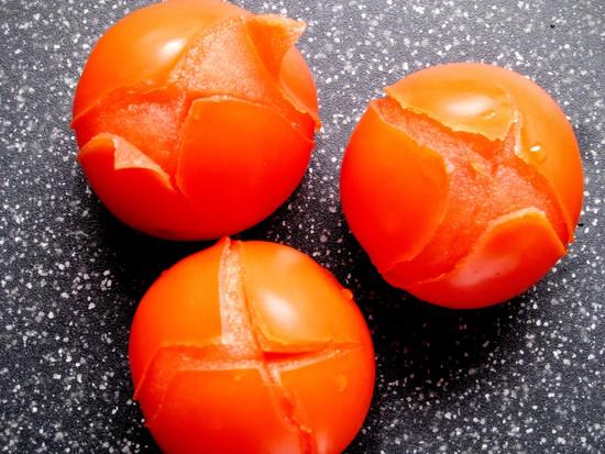 Die Tomaten waschen und auf der Unterseite kreuzweise einschneiden. Wenn das Wasser kocht die Tomaten solange hineingeben, bis sich die Schale zu lösen beginnt. Mit Hilfe der Schaumkelle die Tomaten aus dem kochenden Wasser holen. Kurz abkühlen lassen und vollständig schälen.