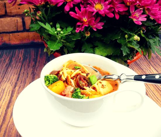 Die Suppe auf die Teller füllen, mit dem Basilikum, den Tomaten und den Mandelsplittern anrichten.