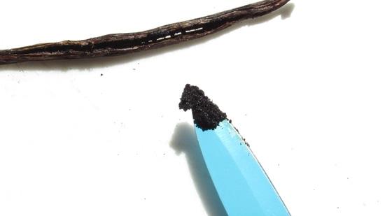 Für die Heidelbeerkonfitüre die Vanilleschote mit der Rückseite des Messers etwas flachdrücken. Dann die Vanilleschote der Länge nach mit dem Messer halbieren. Anschließend mit der Rückseite des Messers das Vanillemark aus den Vanilleschotenhälften herauskratzen und zu den Heidelbeeren in den Topf geben.