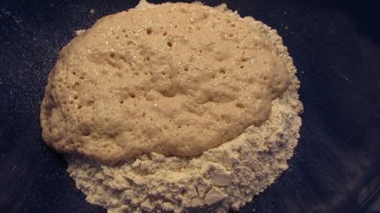 Wenn der Vorteig sein Volumen vergrößert hat, wird der Teig weiterverarbeitet. Dafür muss man ein Ei trennen, das Eigelb in ein Schälchen geben und das Eiweiß gibt man zum Vorteig. Man fügt nun außerdem das Salz, die restliche Milch, die restlichen Eier, den Zucker, die Butter, den Zironenschalenabrieb, das Maismehl, den Rosmarin sowie die Aprikosenstücke hinzu  und verknetet den Teig dabei von Hand (oder aber mit Hilfe eines Handrührgerätes mit Knethaken) zu einer Kugel. Tipp: Den Teig, der an den Händen klebt, kann man leicht mit etwas Mehl lösen. Die Kugel aus der Schüssel nehmen und etwas Mehl in die Schüssel geben, damit sich der Teig nach dem Aufgehen leichter aus der Schüssel nehmen lässt. Die Teilkugel dann wieder in die Schüssel legen.