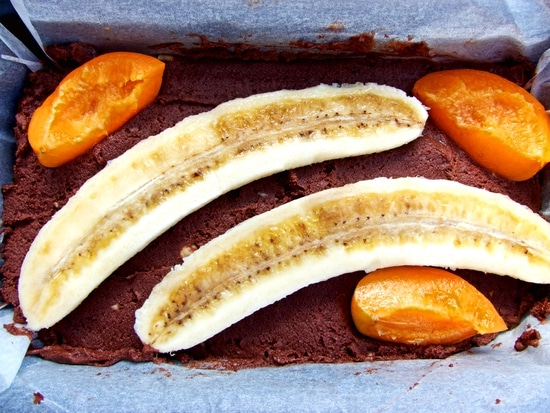 Alles in die vorbereitete Kastenbackform geben und die Bananenhälften oben auf den Teig legen. Wer mag, legt noch andere Früchte auf den Teig. Ich habe noch ein paar frische Aprikosenviertel dazugegeben.