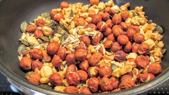 In der Zwischenzeit die Nüsse, Sonnenblumenkerne sowie die Kürbiskerne in die Pfanne geben und ohne Fett  rösten. Tipp: Hierbei löst sich die Schale von den Haselnüssen. Wer dies nicht mag, röstet die Haselnüsse einfach nicht.