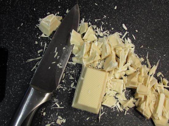 Wenn die Eisbärtatzen fertig sind, muss man sie auskühlen lassen, bevor man sie mit der Kuvertüre überzieht. Während die Tatzen auskühlen, wird die Kuvertüre zubereitet. Dafür die Kuvertüre zunächst in kleine Stücke schneiden.