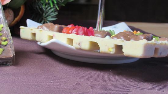 Abschließend die Rückseite der Schokolade mit Gummibärchen und/oder kleinen Schokoladen Schneemännern garnieren.