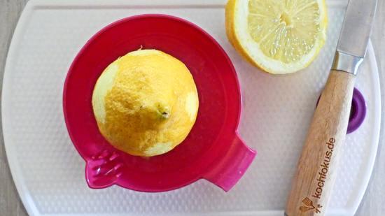 Die Zitrone nun halbieren und beide Hälften auspressen. Den Saft der Zitrone sowie die abgeriebene Zitronenschale zu der Mischung aus Bananen, Eiern, Joghurt und Rapsöl hinzufügen und unterrühren.